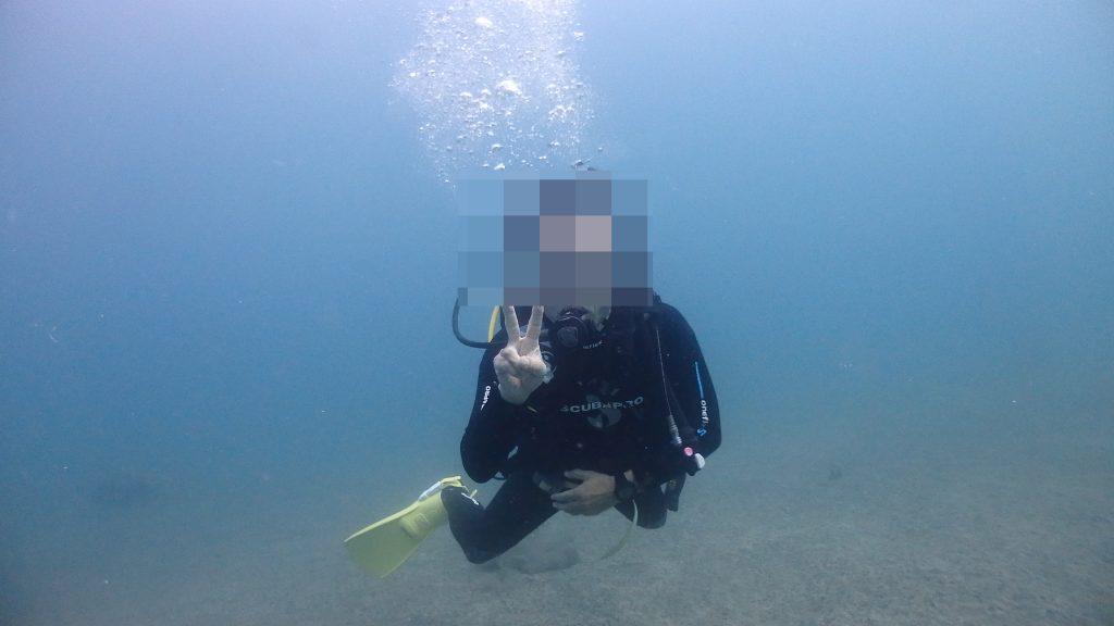 リフレッシュダイビング中、浅い水深で水になれてカメラにピースサインするダイバー