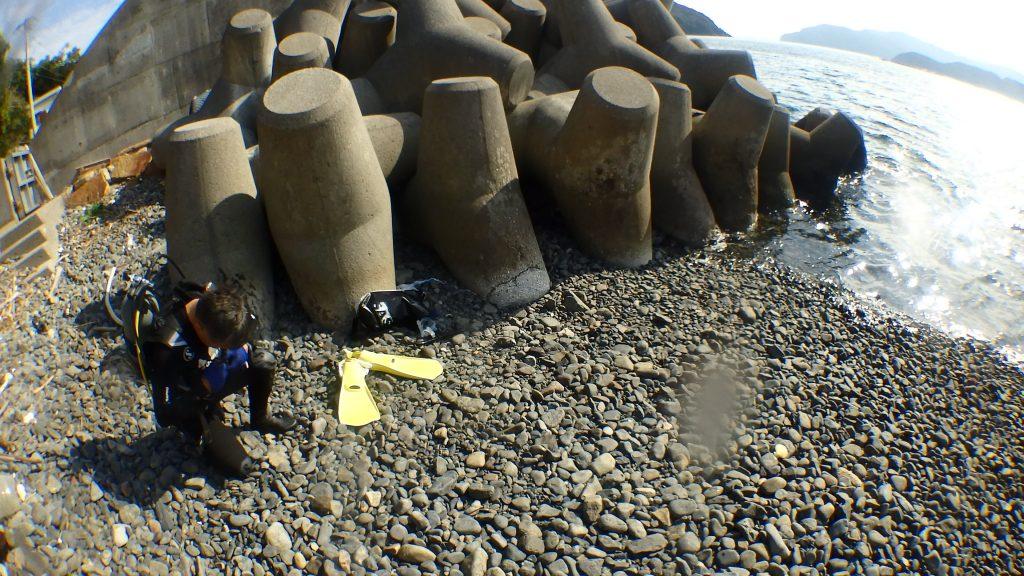 浜辺で水中へ入る準備を整えるダイバー。満ち潮を失念していて防水バックが流されそうになりました
