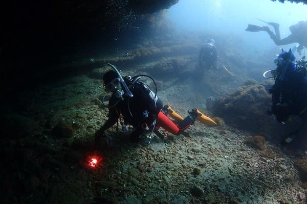 水中の岩でできたオーバーハング状の地形の暗がりに入り、ライトで中を照らすダイバー