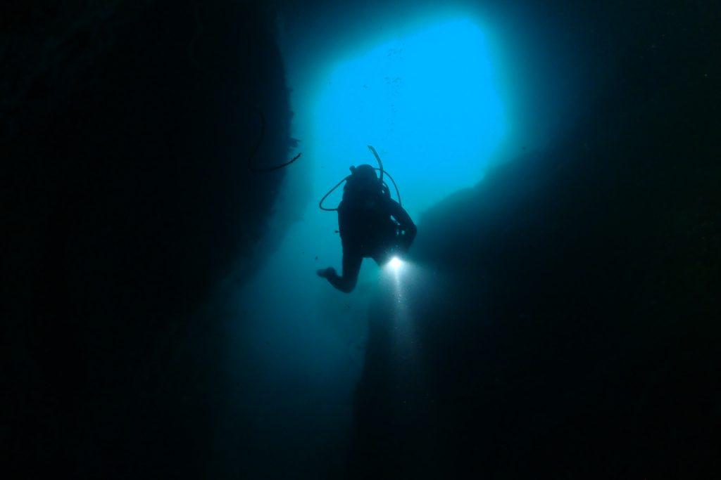 真っ暗闇の洞窟を進むダイバーの後ろには、洞窟の入り口から漏れた光が青く光ってとても綺麗な風景に。