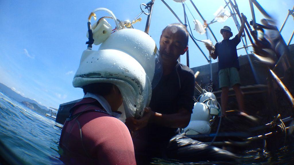 シーウォーカーで水中へ入る直前。上からヘルメットが下りてくる瞬間、ヘルメットをスタッフが支えています。