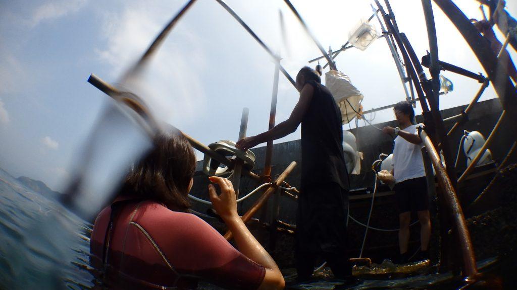 シーウォーカーで海に入る前、スタッフの準備を海に入って待っている女性の体験者。