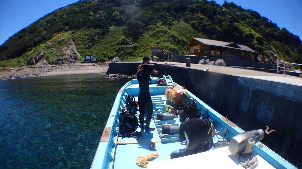 体験ダイビングの前に、ボート上で準備をする二人の旅行者。すでにウエットスーツに着替えて後は機材を背負って海に入るだけです。