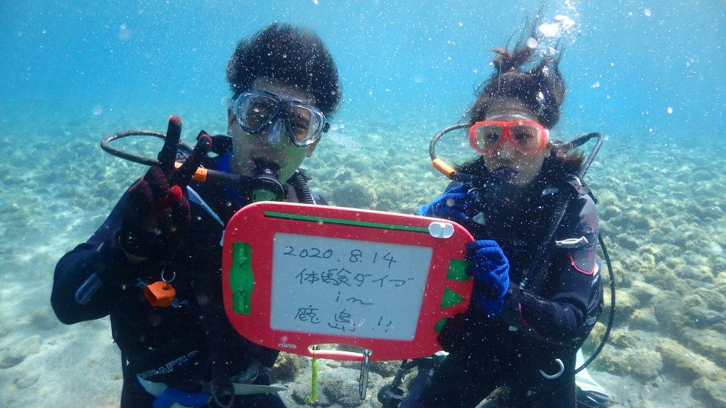 透明度がよい海中で二人の記念撮影。磁石で文字をかけるボードには「2020.8.14体験ダイビングin鹿島」と書かれています。