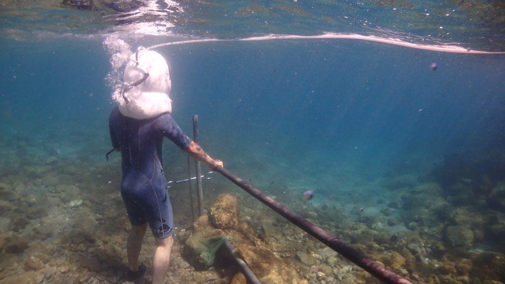 シーウォーカーで海中にみんなが揃うのを待っている体験者。水中には沖に向かって手すりが伸びているので、それを握っておけば安心です。