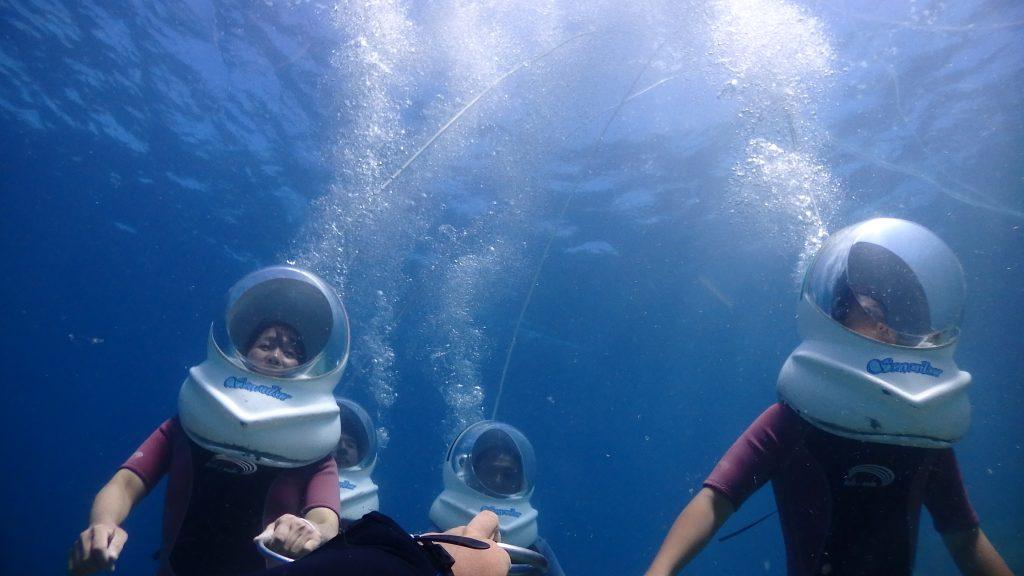 水深4mはある場所で記念撮影。皆さんが歩いている最中に、下方向から水面を入れて撮影しました。浮かび上がる泡と地上から延びたホースが深さを想像させます。