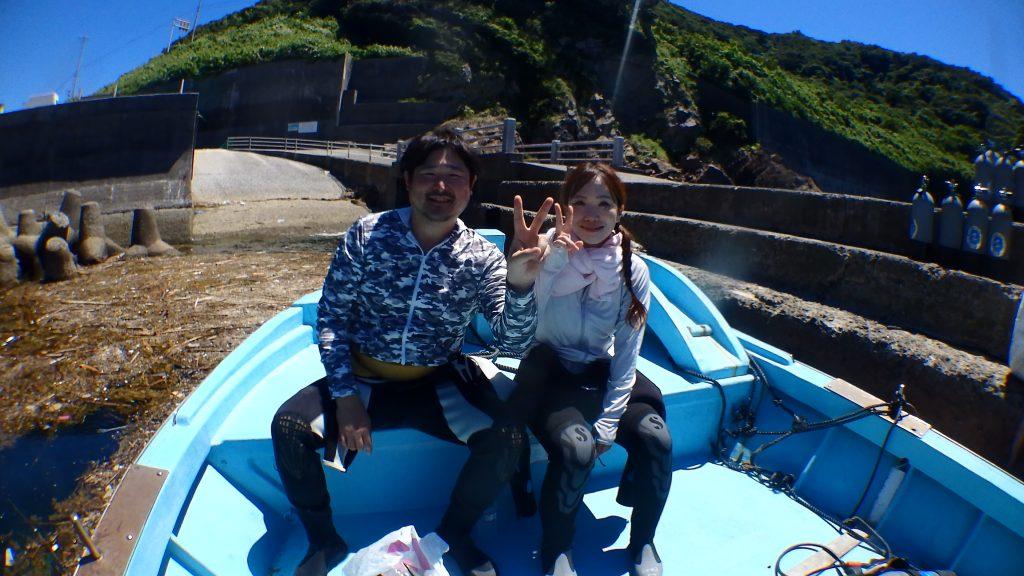 体験ダイビングの前に、船上で記念撮影を行う二人の旅行者