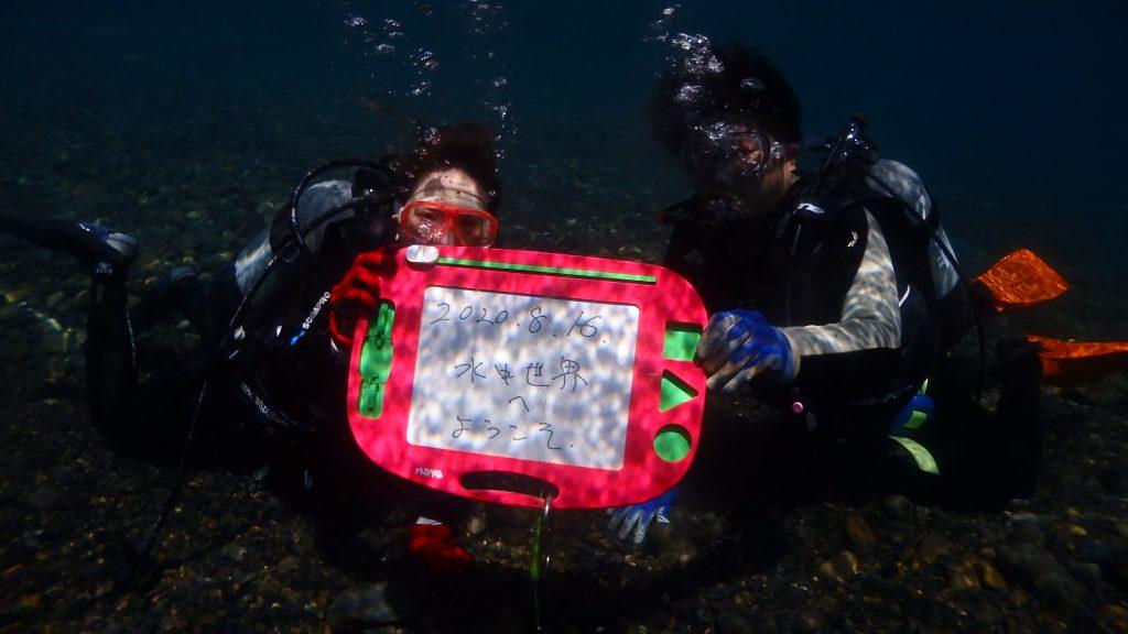 水中で記念撮影をするときには、お絵かきボードを持って写真を撮ります。ボードには今日の日付「2020年8月16日」と「水中世界へようこそ!」と書かれています。