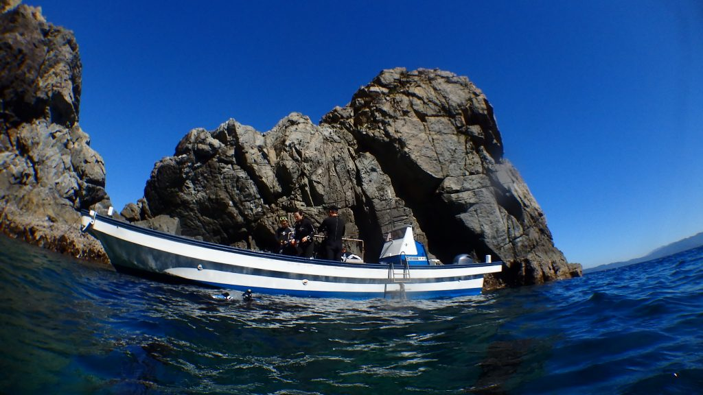ダイビングポイント小横島の前にアンカリングする船を水面から撮影。数名のダイバーが準備をしている様子が見える