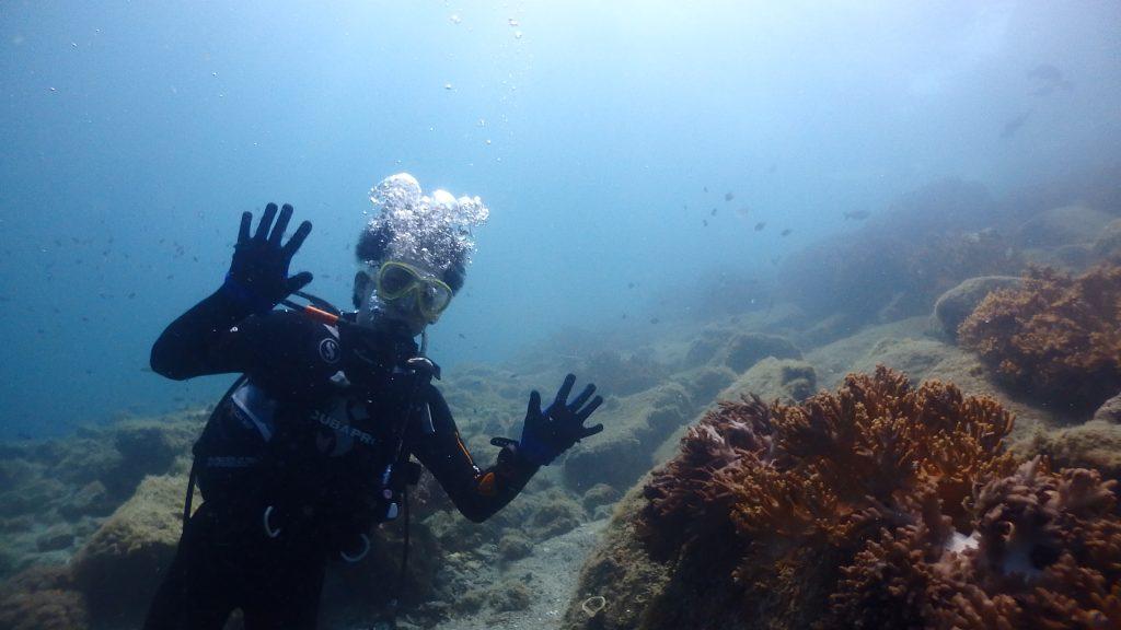 Sさんの記念写真、海底にはユビノウサンゴと呼ばれるサンゴが群生しています。