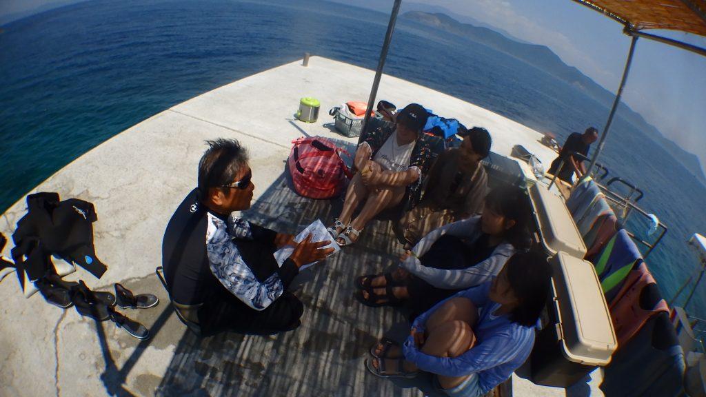 体験ダイビングは無人島「鹿島」で行います。この日は鹿島の桟橋で4名の女性が体験ダイビングの説明を聞いています。