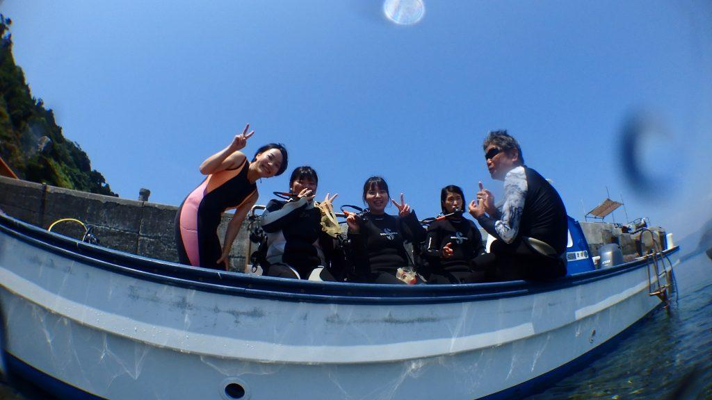 水面からボート上で説明を聞いている4人組の女性を撮影。インストラクターが説明中ですが、皆さんこちらに向かってピースをしています。