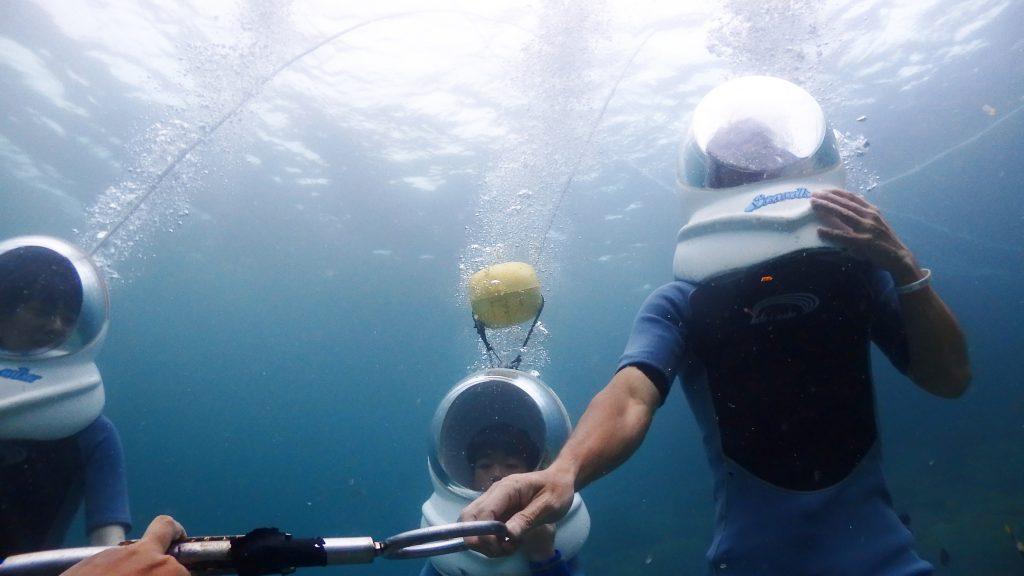 シーウォーカーの体験風景を海底付近から上に向かって撮影すると、ヘルメットからあふれ出る泡が海面に向かって登っていく様子が綺麗にうつります。