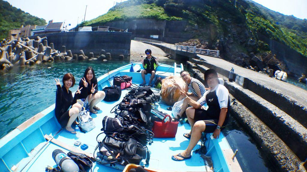 体験ダイビングの前に、ボート上で記念撮影。5名の旅行者がダイビングの準備を整えてボート上で出発を待っています。