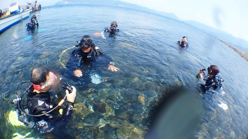 体験ダイビング開催地の無人島「鹿島」。インストラクターの男性がみんなの中心で呼吸の練習を促しています。