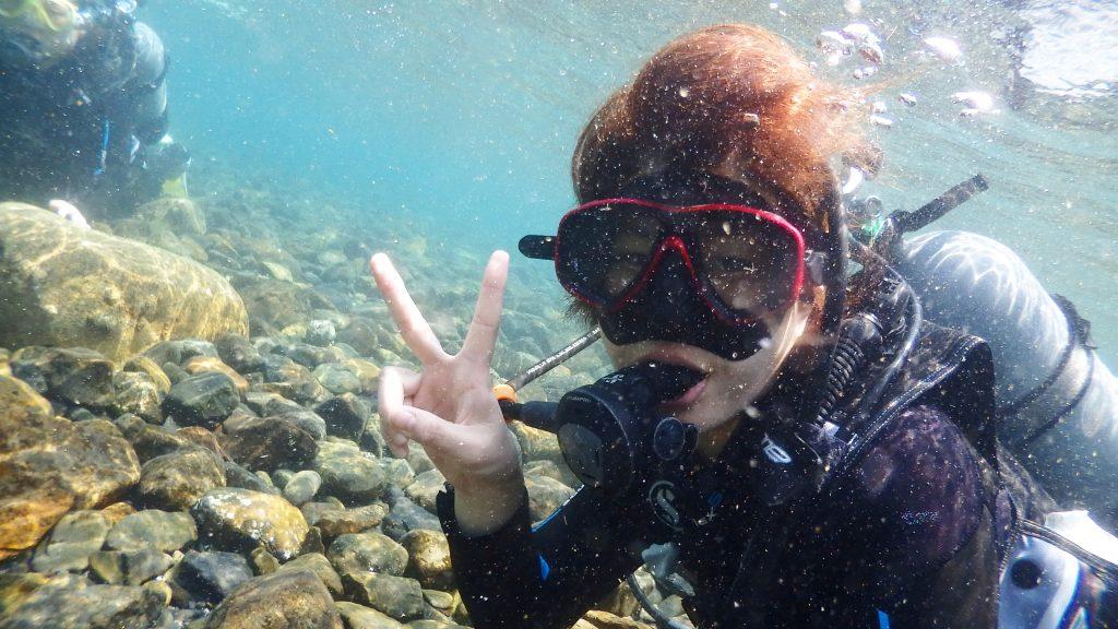 浅い場所での呼吸の練習は余裕なのか、水中で楽しそうにピースサインをする女性。