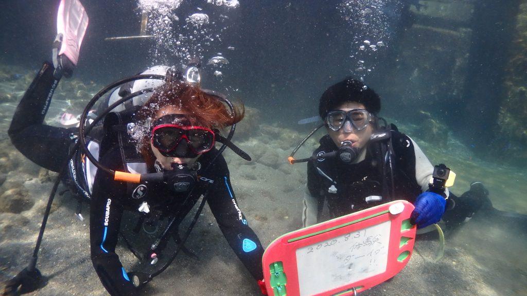 体験ダイビングの初めには、水中で文字が書けるお絵かきボードを持って記念撮影。お二人でお持ちいただいたボードには2020.8.31「体験だーいぶ」と書かれています。