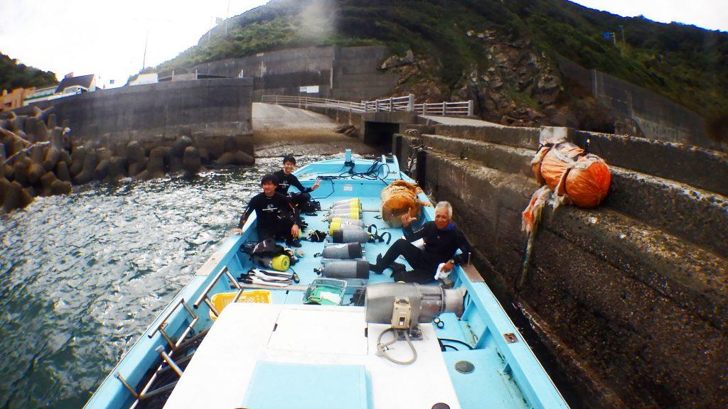 体験ダイビングの前、出発直前のダイビングボートで記念写真。三人の男性がこれから海に潜る準備をしています。