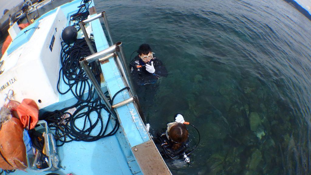 重い装備を背負って海中へ入る体験ダイバーの二人。とても慣れている様子で、水面に浮かんでいます。