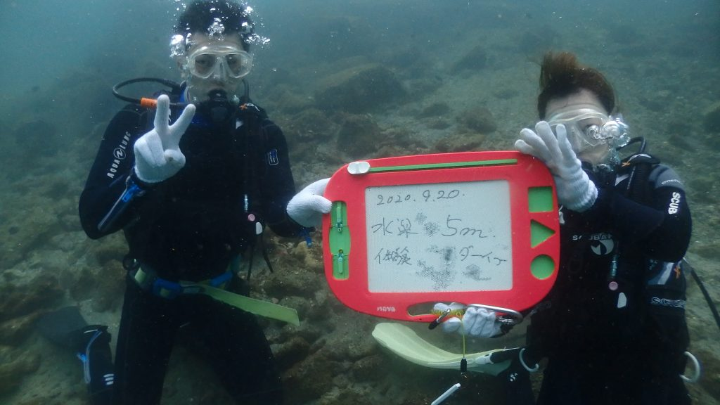 水が怖くないと言っていたお二人は、簡単に水深5mまで入っていました。そこで磁石で文字が書けるボードに今日の日付を書いて、記念撮影をしました