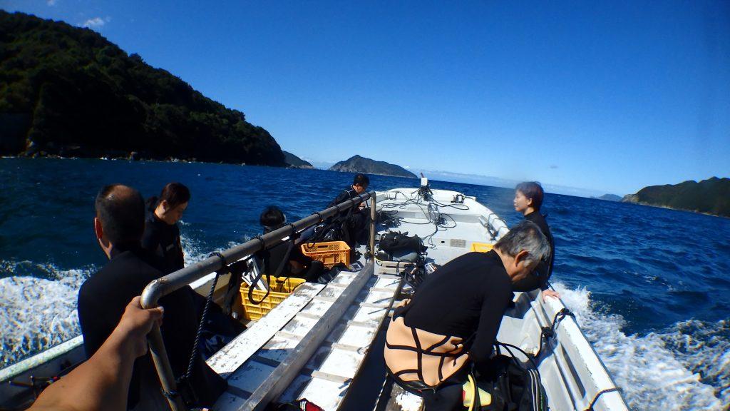 ファンダイビングの皆様と一緒に、オープンウォーター講習の最終日を迎えるお二人がボートで移動する風景。正面には無人島鹿島が見え、波を切ってボートが進む