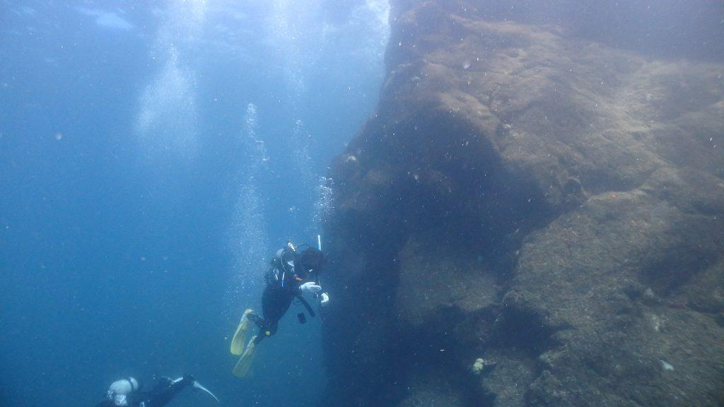水底から水面まで伸びる岩が印象的なダイビングポイント。そびえたつ岩の周りを二人のダイバーが魚を探しながら泳いでいます。