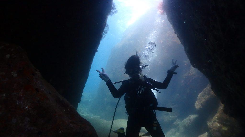 洞窟になっている場所を潜り抜けて目的地に到達しようとしているダイバーが両手を開いてピースサインをこちらに送っています