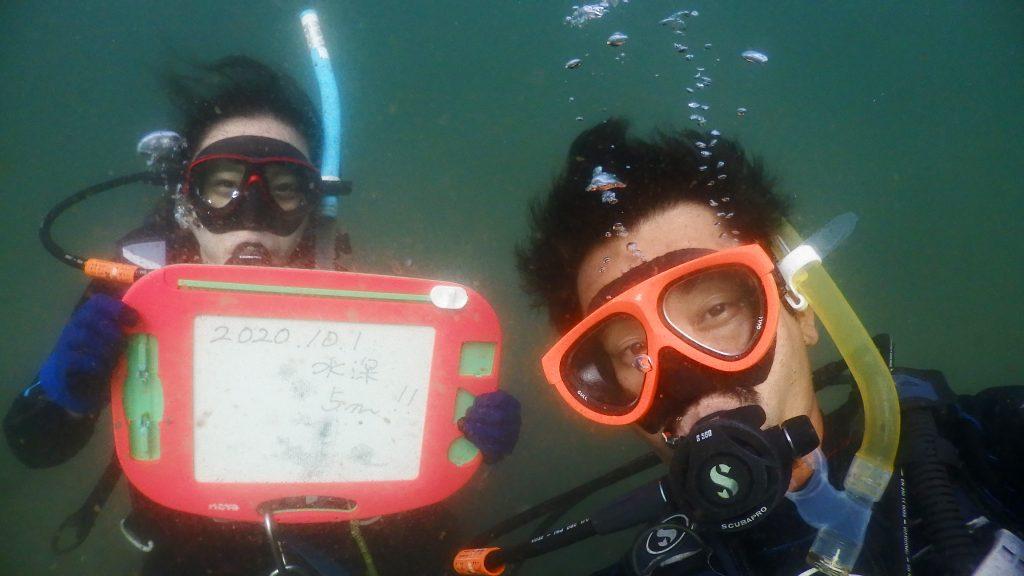 インストラクターが自撮りをしながら、講習生と記念撮影。後ろのお絵かきボードには水深5mと書かれています。