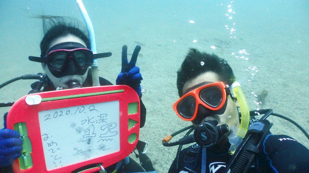 海洋実習へ入ったら、水深12mまで進みます。問題なく12mまで潜れた女性の講習生は笑顔で記念撮影をしています。