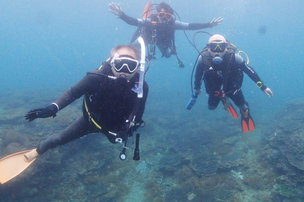 水中を漂いながら、3人で水中記念撮影。背後には広い範囲に広がるサンゴ群生が見えています。