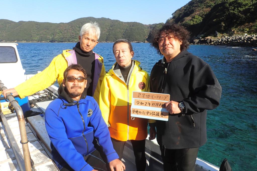 サンゴ保全活動の前には必ず集合写真を撮影します。ダイビング活動前に、船の上で一か所に集まって、この日の日付と活動場所が書かれたプラスティックボードを持ちながらみんなで撮影。