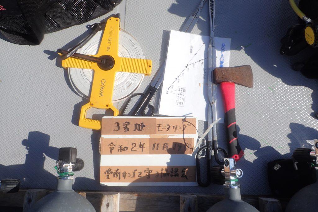この日に使用した道具も全て撮影して記録に残しておきます。100mを計測するためのメジャーや、濡れても平気な紙に書かれた海底の地図やハサミ、オノなどを一か所にまとめておきます。